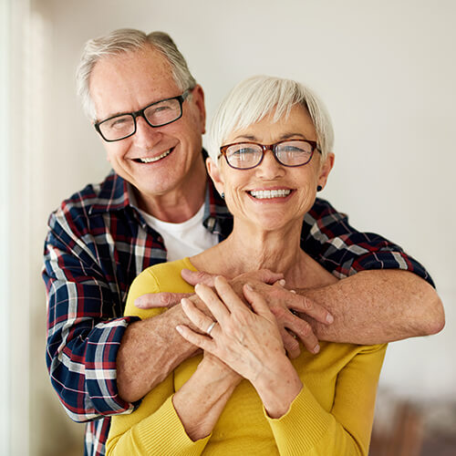 Image of a elderly couple smiling and hugging indoors