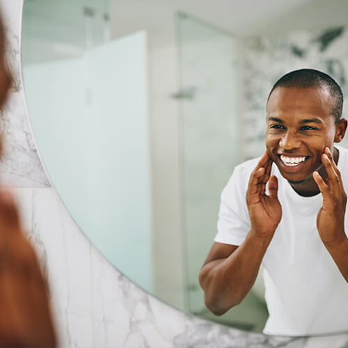 Image of a man looking at his brand new smile at the mirror