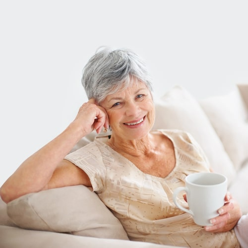 Older woman with grey hair sitting on the sofa while holding a cup and smiling
