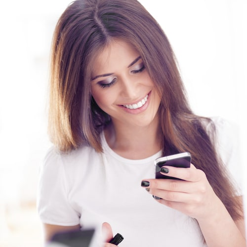 Girl with long brown hair, looking at he phone and smiling